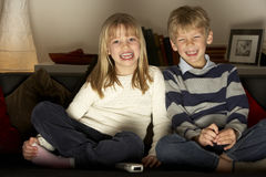 Brother And Sister Watching Television Stock Photography