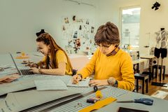 Brother and sister wearing bright yellow clothes drawing sketches. Drawing sketches. Cute active brother and sister wearing bright yellow clothes drawing royalty free stock photo