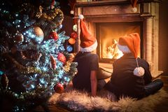 Back view, brother and sister wearing Santa`s hats warming next to a fireplace in a living room decorated for Christmas. Brother and sister wearing Santa`s hats royalty free stock photos