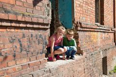 Brother and sister were left alone as a result of military conflicts and natural disasters. Children in a ruined and abandoned. House. Staged photo royalty free stock photo