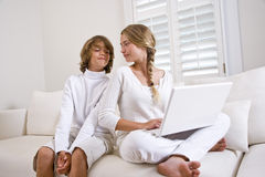 Brother and sister in white on sofa using laptop Royalty Free Stock Photography