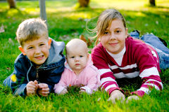 Brother with sisters. Brother with two sisters lying on grass and smiling stock photo