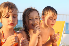 Brother and sisters on beach eating ice cream. Little brother and two sisters in swimsuits on beach eating ice cream after bath. focus on girl in middle Royalty Free Stock Photography