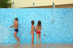 Brother and sisters in bikinis taking shower. Little brother and two sisters in bikinis taking shower after swimming Stock Photo