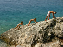 Brother and sisters climbing. Brother and sisters (best friends) climbing on the cliff by the Adriatic sea (Croatia Dalmatia). Horizontal color photo Royalty Free Stock Photo