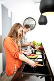 Brother and sisters cooking meal together. Stock Image
