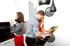 Brother and sisters cooking meal together. Stock Photography
