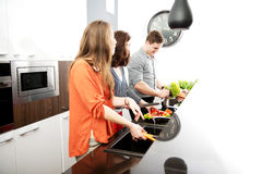 Brother and sisters cooking meal together. Royalty Free Stock Photography