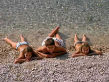 Brother and sisters lie on the beach Stock Photography