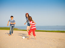 Brother and sisters play with a beach ball outdoors Royalty Free Stock Photos