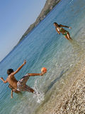 Brother and sisters playing football in the sea Stock Image