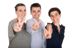 Brother and sisters showing victory sign. Happy smiling brother and sisters showing showing victory hand sign (isolated on white background Royalty Free Stock Photos