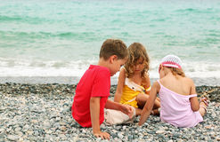 Brother and sisters are sitting on beach Stock Photos