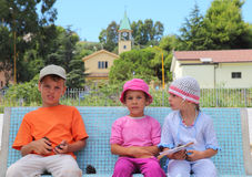 Brother and sisters are sitting on bench Royalty Free Stock Images