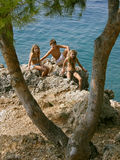 Brother and sisters on summer holidays. Brother and sisters spending summer holidays on the stone between the branches of the tree at Adriatic sea (Croatia Stock Photos