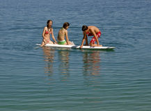 Brother and sisters on surf desk. Boy and girls enjoy in summer vacation in Adriatic  Omis (Croatia, Dalmatia Royalty Free Stock Image