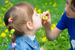 Brother spraying nose his sister. Outdoors Royalty Free Stock Images