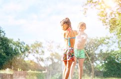 Brother sptays his slittle sister water from garden hose. Children have fun in hot summer day stock photo
