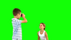 Brother taking pictures of his sister jumping on green screen Royalty Free Stock Images