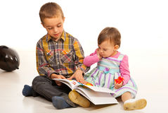 Brother teaching his sister. Brother teaching his little sister and showing from a book Royalty Free Stock Photos