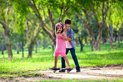 Brother teaching sister how to ride a board Royalty Free Stock Photography
