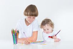 Brother and toddler sister paiting in white room Royalty Free Stock Image