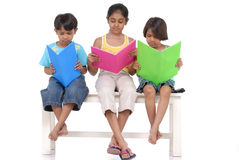 Brother and two sister reading books Royalty Free Stock Photo