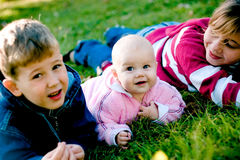 Brother with two sisters. Lying on grass and smiling stock photo