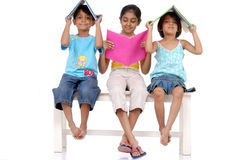 Brother and two sisters holding books. Twins brother and sisters sitting with elder sister holding books over head sitting on bench Stock Images