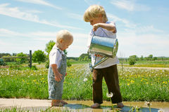 Brother Watering Baby Royalty Free Stock Image