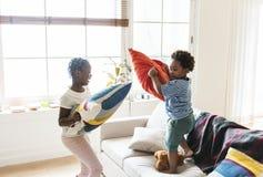 Brother y almohada de la hermana que lucha en sala de estar fotografía de archivo