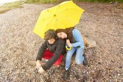 Brother y hermana con el paraguas amarillo Imágenes de archivo libres de regalías