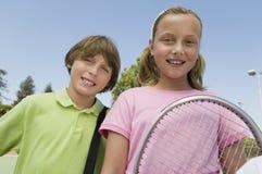 Brother y hermana con la estafa de tenis en el cierre del retrato del campo de tenis para arriba fotografía de archivo libre de regalías