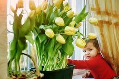 Brother y hermana con las flores Tulipanes en la ventana imagenes de archivo