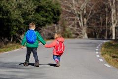 Brother y hermana con las mochilas que caminan en el camino Imagen de archivo
