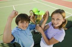 Brother y hermana en campo de tenis que soportan la opinión de alto ángulo del retrato del trofeo foto de archivo