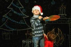 Brother y hermana en fondo de la Navidad, jugando con una paleta y los cepillos Feliz Navidad Foto de archivo libre de regalías