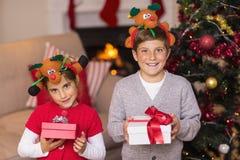 Brother y hermana en la venda que sostiene el regalo Foto de archivo