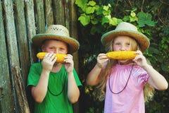Brother y hermana en sombreros de paja que comen el maíz en el aire fresco Fotografía de archivo libre de regalías