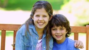 Brother y hermana que abrazan en banco de parque almacen de metraje de vídeo
