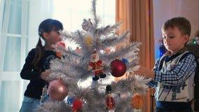 Brother y hermana que adornan el árbol de navidad metrajes