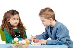 Brother y hermana que adornan los huevos de Pascua Imágenes de archivo libres de regalías