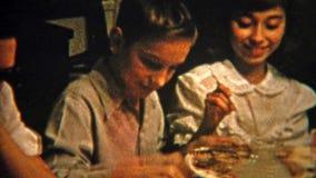 1951: Brother y hermana que comparten la comida en la tabla de cena NEWARK, NEW JERSEY metrajes