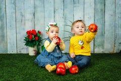 Brother y hermana que juegan en césped Imagen de archivo libre de regalías