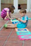Brother y hermana que juegan en el patio trasero Foto de archivo libre de regalías