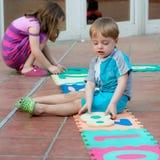 Brother y hermana que juegan en el patio trasero Foto de archivo