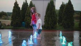 Brother y hermana que juegan en la fuente coloreada junto Chorro de agua conmovedor del muchacho y de la muchacha, divirtiéndose almacen de video