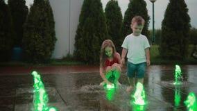Brother y hermana que juegan en la fuente coloreada junto Chorro de agua conmovedor del muchacho y de la muchacha, niños mojados  almacen de metraje de vídeo