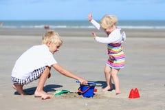 Brother y hermana que juegan en la playa Imagenes de archivo