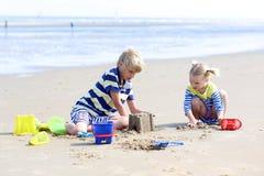 Brother y hermana que juegan en la playa arenosa Imagen de archivo libre de regalías